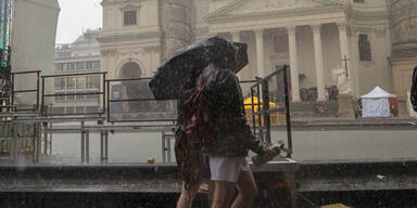 Menschen mit Regenschutz in Wiener Innenstadt