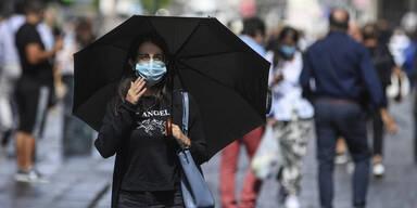 passantin mit regenschirm und maske in corona-krise