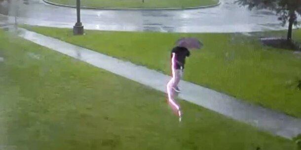 Blitz schlägt direkt neben Fußgänger ein
