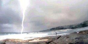 Blitz schlägt neben Frau am Strand ein