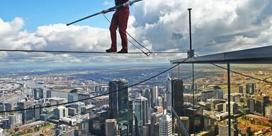 Hochseil-Artist Kane Peterson spaziert 300 Meter über dem Eureka Sonnendeck in Melbourne