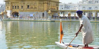 Ein Mann säubert das Wasser beim Goldenen Tempel in Amritsar (Indien)